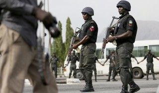 Police officers patrol near a journalist during a protest in Abuja