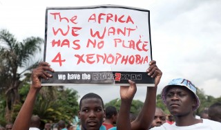 Foreign nationals hold a placard during an anti-xenophobia march outside the City Hall of Durban on April 8, 2015. Hundreds of people marched today to protest against anti-immigrant violence, a week after hundreds were attacked near the eastern city of Durban. Most of the 250 victims of the latest outbreak of xenophobic violence at Isipingo, south of the Indian Ocean city, come from the Democratic Republic of Congo.  AFP PHOTO / RAJESH JANTILAL