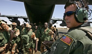 A US Airman of the 322nd Air Expeditionary Group of the 3rd Air Forces based in Rumstein, Germany, watches 31 October 2014 Rwandan troops of the African Union Cease Fire Commission arriving with a USAF C-130 in  El-Fasher, Sudan. One hundred Rwandan troops arrived in the Darfur town of El Fasher today as part of an expanding African Union (AU) mission monitoring a shaky ceasefire for the conflict-ravaged province in western Sudan. AFP PHOTO/MARCO LONGARI