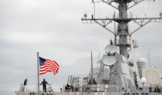 A US Marine stands beneath a flag aboard the USS Bainbridge, as it approaches a berth upon arrival in the port of Mombasa on April 16, 2009. The US Navy vessel was escorting a US merchant ship unsuccesfully attacked by Somali pirates in the Indian Ocean a day earlier. Also onboard was Captain Richard Phillips of the US merchant ship Maersk Alabama who was rescued after a dramatic intervention in his kidnapping by Navy sharpshooters aboard the Bainbridge. AFP PHOTO/Roberto SCHMIDT
