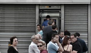 People stand in a queue to use ATM machines to withdraw cash at a bank in Athens on June 27, 2015. Greece will hold a referendum on July 5 on the outcome of negotiations with its international creditors taking place in Brussels on June 27, Prime Minister Alexis Tsipras announced. AFP PHOTO/ ARIS MESSINIS