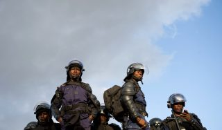 """Congolese riot-police stand guard in Lubumbashi's city centre, following the announcement of the provisional results of the Democratic Republic of the Congo's presidential election on December 9, 2011. Around 1500 police and 64 military police have been deployed in the city during the election period, as well as the army in """"strategic points"""". The Independent National Electoral Commission declared today that Kabila won his native Katanga province with 89.97% of votes, winning the country's elections with 48.95% nationally.    AFP PHOTO/ PHIL MOORE / AFP / PHIL MOORE"""