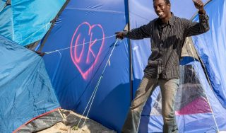 "A migrant smiles next to a tent tagged with the initials of the United Kingdom, UK, into a heart-shape logo inside the ""Jungle"" camp for migrants and refugees in Calais on June 24, 2016. Eurosceptics are triumphant on June 24, 2016 after Britain voted to leave the EU and swiftly demanded referendums in their own countries, amid growing concerns Europe's hard-won unity may start to crumble away. Britons voted 52 percent to 48 percent to quit the bloc, a margin of more than one million votes, according to final results from Thursday's referendum.  / AFP PHOTO / PHILIPPE HUGUEN"