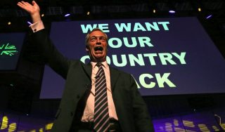 """Leader of the United Kingdom Independence Party (UKIP), Nigel Farage, waves to the audience at a public meeting of the EU Referendum campaign in Gateshead, north east England on June 20, 2016. Divisions have surfaced among pro-Brexit campaigners after UK Independence Party leader Nigel Farage released a poster last Thursday showing immigrants trudging through Europe with a headline in red: """"Breaking Point"""". On that same day, Cox, a 41-year-old mother of two and pro-EU, was on her way to meet members of the public in northern England when an attacker shot and stabbed her, leaving her bleeding on the pavement. She died of her wounds.  / AFP PHOTO / SCOTT HEPPELL"""