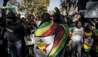 "Zimbabwean ""ThisFlag"" activists arrive in Pretoria on July 14, 2016 to take part in a march towards the Zimbabwean embassy. The Zimbabwean pastor who has emerged as leader of a new protest movement against President Robert Mugabe's authoritarian government called on July 14, 2016 for further strikes and shutdowns. Mawarire, who started the popular ThisFlag internet protest campaign, was one of the organisers of a day-long nationwide strike last week that closed offices, shops, schools and some government departments.  / AFP PHOTO / MARCO LONGARI"