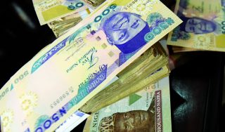 This picture taken on January 28, 2016 in Lagos shows naira banknotes, Nigeria's currency.  Nigeria's central bank governor, Godwin Emefiele, on January 26 dismissed calls to devalue the naira in his monetary policy committee statement. Instead he chose to continue propping up the currency at 197-199 naira to the dollar and maintain foreign-exchange restrictions. As a result, the naira on the black market is hovering around a record low of 305, fuelling complaints from domestic and foreign businesses who can't access dollars required for imports.  / AFP PHOTO / PIUS UTOMI EKPEI