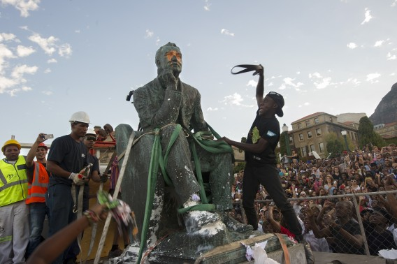TOPSHOTS Students attack the defaced statue of British mining magnate and politician, Cecil John Rhodes, as it is removed by a crane from its position at the University of Cape Town on April 9, 2015, in Cape Town. Black students celebrated the fall of a statue of the British colonialist at the university as some white groups protested what they see as threats to their heritage. Cheers went up as a crane removed the huge bronze statue from its plinth at South Africa's oldest university after a month of student demonstrations against a perceived symbol of historical white oppression.             AFP PHOTO / RODGER BOSCH