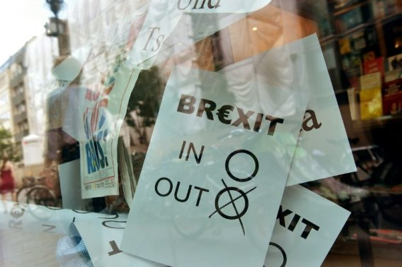 """A poster featuring a Brexit vote ballot with """"out"""" tagged is on display at a book shop window in Berlin on June 24, 2016. Britain has voted to break out of the European Union, striking a thunderous blow against the bloc and spreading panic through world markets on June 24 as sterling collapsed to a 31-year low.  / AFP PHOTO / John MACDOUGALL"""