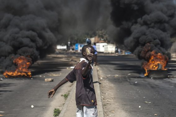 A protester throws rocks next to burning tyres during a demonstration on July 6 2016, in Bulawayo Zimbabwe. Residents clashed with police after the arrest of two political activists staging a protest in the City centre. Zimbabwe police fired warning shots and teargas as a protest strike against President Robert Mugabe's economic policies gripped the country Wednesday, closing businesses and crippling public transport. The strike follows days of unrest over the government's failure to pay civil servants' salaries, a currency shortage, import restrictions and multiple police road blocks reportedly extorting cash from motorists.  / AFP PHOTO / STRINGER