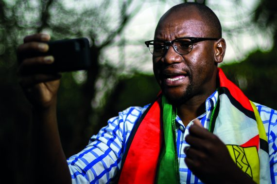 """This photo taken on May 19, 2016 in Harare shows Zimbabwean cleric Evan Mawarire, wrapped in the Zimbabwean National flag, recording an instalment of his #ThisFlag video series, in which he decries the government's failure to provide basic services and stem economic decline and corruption in the country.  In this gloomy climate, Pastor Evan Mawarire has emerged in recent weeks as a national hero, after having launched his campaign """"ThisFlag"""", which has becomeme an unlikely outlet for many frustrated Zimbabweans. / AFP PHOTO / Jekesai Njikizana"""