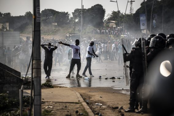 Supporters of Gabonese opposition leader Jean Ping demonstrate in front of security forces blocking them as they try to reach the electoral commission in Libreville on August 31, 2016. Bongo won by a narrow 5,594 votes of a total 627,805 registered voters. Turnout was 59.46 percent nationwide but soared to 99.93 percent in one of the country's nine provinces -- the Haut-Ogooue, heartland of Bongo's Teke ethnic group -- in a result hotly contested by the opposition. / AFP PHOTO / MARCO LONGARI