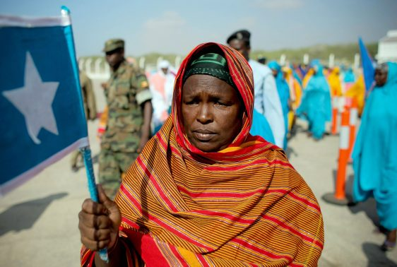 "RESTRICTED TO EDITORIAL USE - MANDATORY CREDIT ""AFP PHOTO / AU-UN IST PHOTO / STUART PRICE"" - NO MARKETING NO ADVERTISING CAMPAIGNS - DISTRIBUTED AS A SERVICE TO CLIENTS In this photograph released by the African Union-United Nations Information Support Team on March 25, 2012, a woman holds the Somali flag at Mogadishu International Airport during a ceremony held to recieve the casket containing the body of fomer Somali president Abdullahi Yusuf Ahmed who died aged 77 on March 23 at a hospital in the Gulf State of Abu Dhabi. AFP PHOTO /AU-UN IST PHOTO / STUART PRICE. / AFP PHOTO / AU-UN / STUART PRICE"