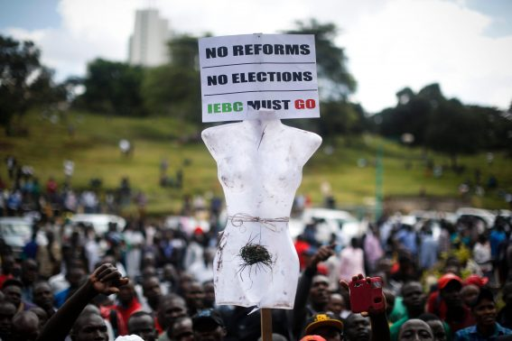 G3AFP0 epa05348719 Opposition supporters hold up a mannequin part with a slogan attached as they listen to their leader during their weekly rally to protest against the country's electoral body Independent Electoral and Boundaries Commission (IEBC) in Nairobi, Kenya, 06 June 2016. Protests in the capital remained relatively peaceful, however, the local media reported that at least two protesters were shot dead in a protest in the western city of Kisumu.  EPA/DAI KUROKAWA