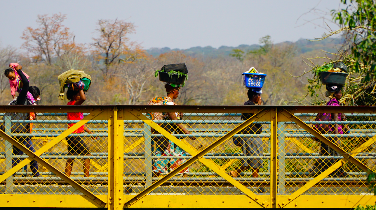 Women cross the border between Zambia and Zimbabwe carrying trays of produce on their heads