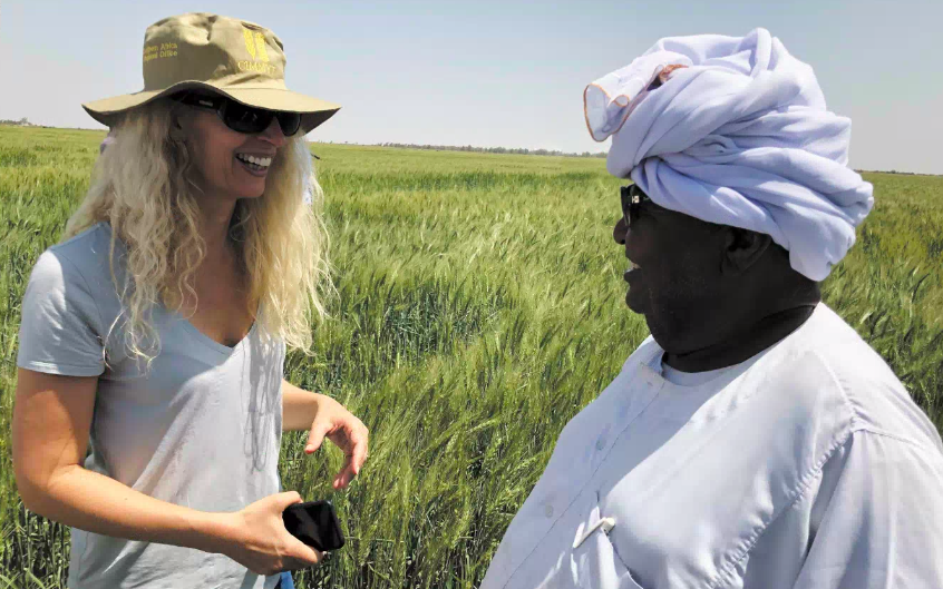 Dr Jennifer Blanke, the African Development Bank's VP for Agriculture, on the left, stands in a field talking to a Sudanese farmer.
