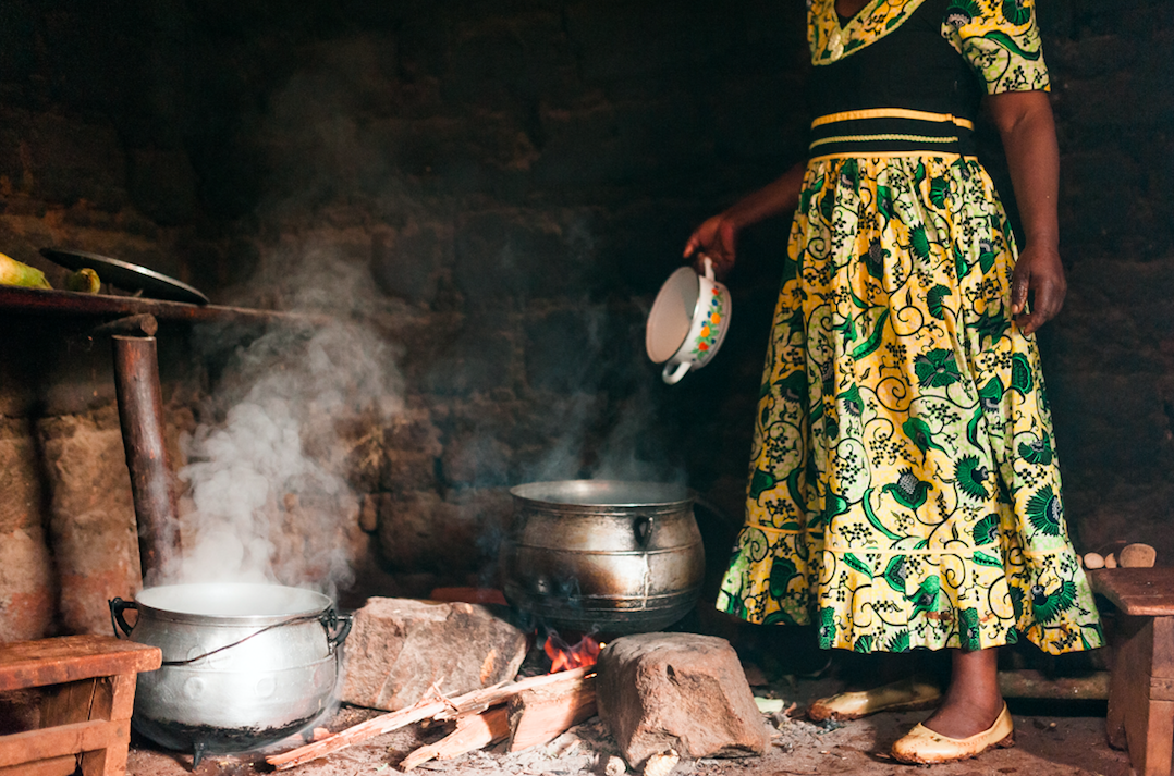 An African woman cooks using traditional utensils