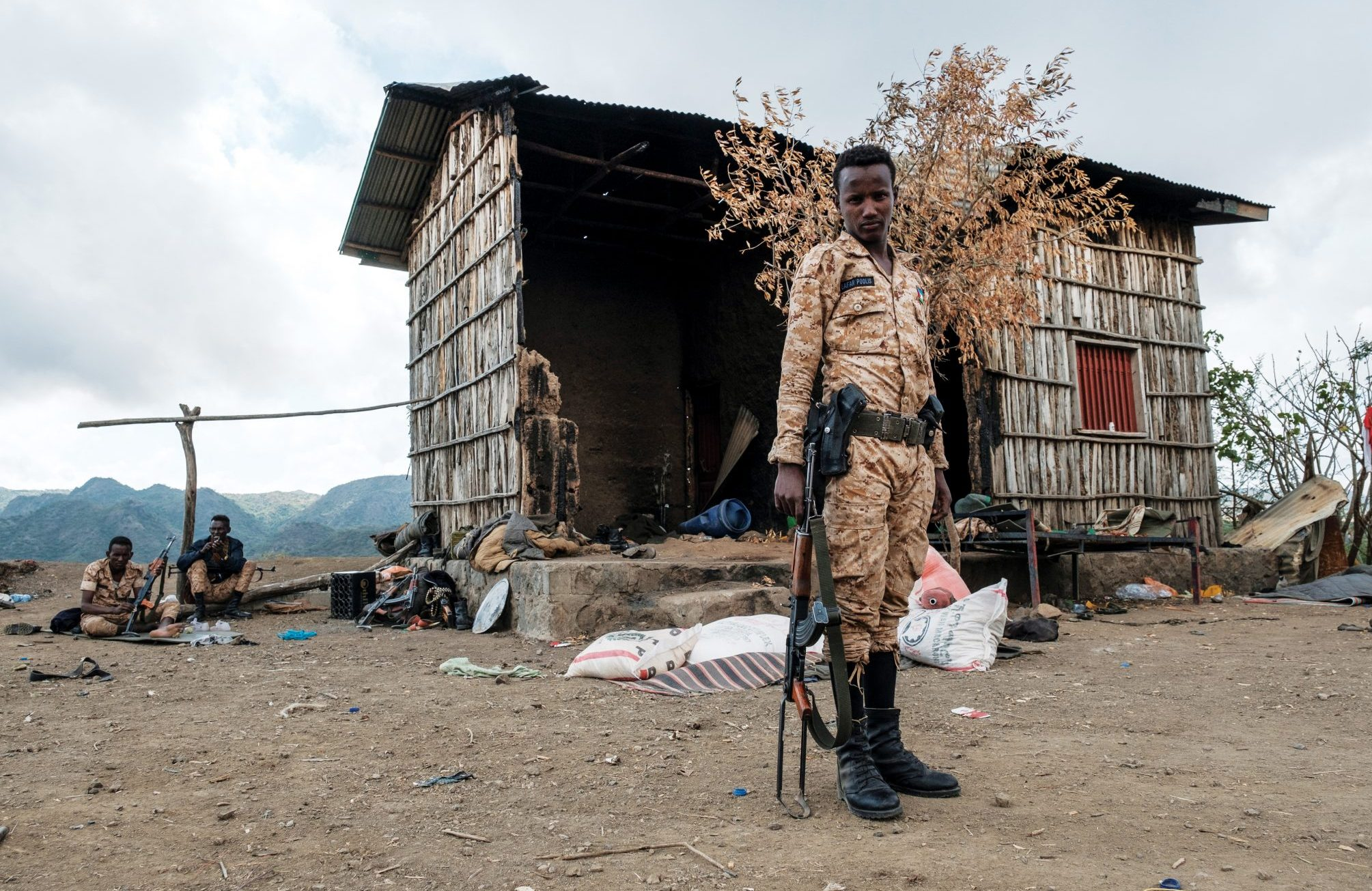 A member of the Afar Special Forces stands in front of a damaged house in the outskirts of the village of Bisober, Tigray.