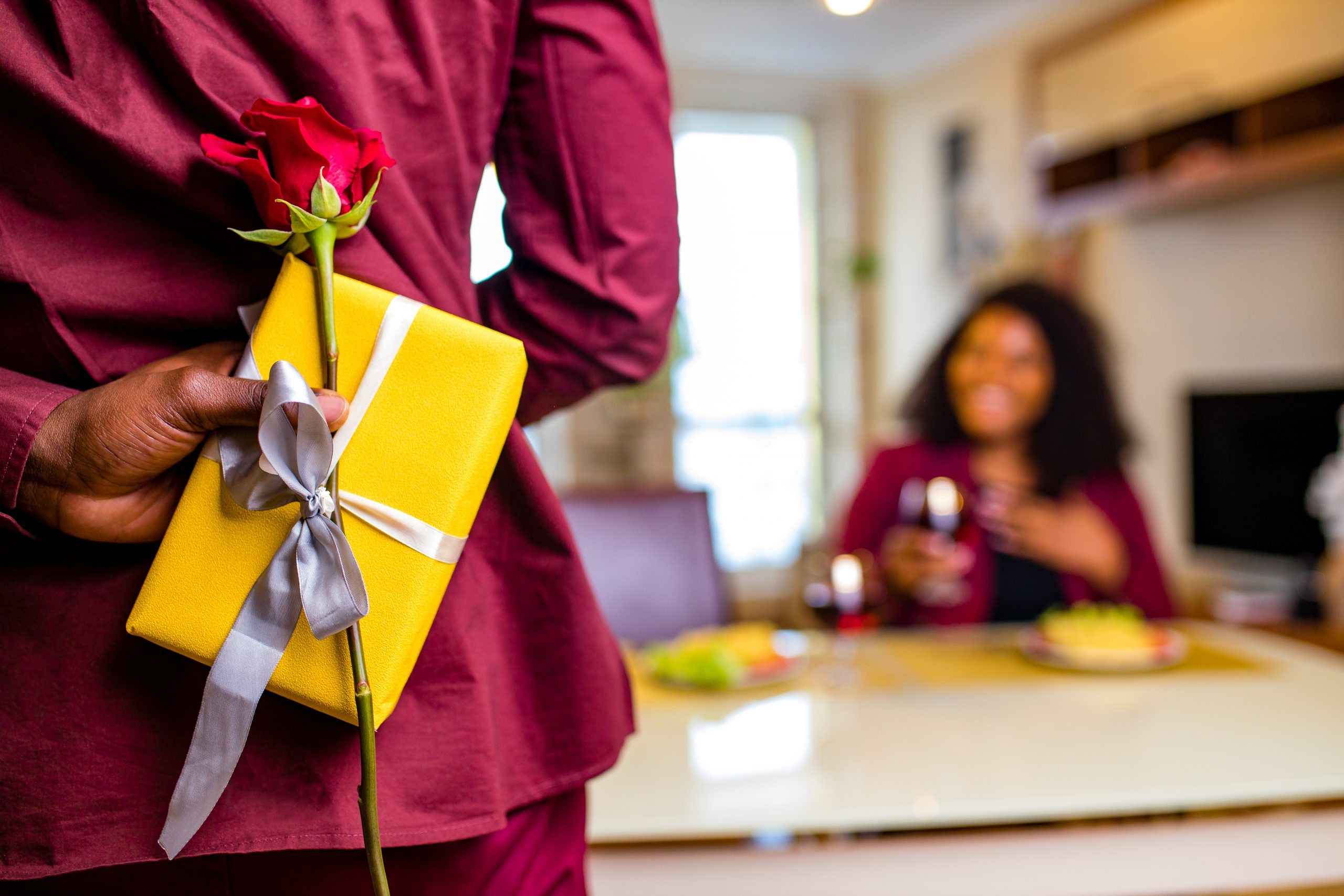 An African man hides behind his back the Valentine's gifts he is about to give his wife.