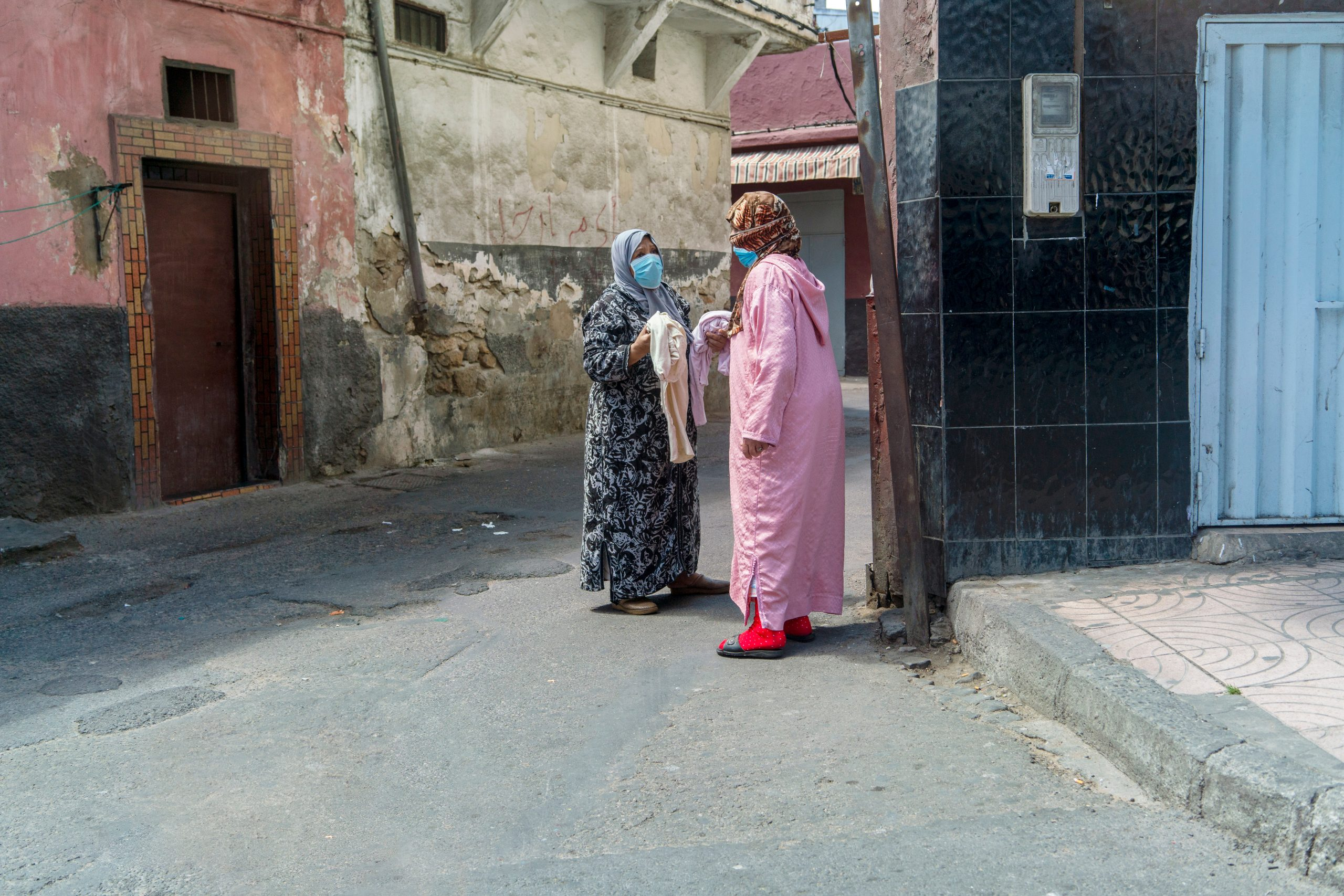 Women in face masks chat in the street in Casablanca.