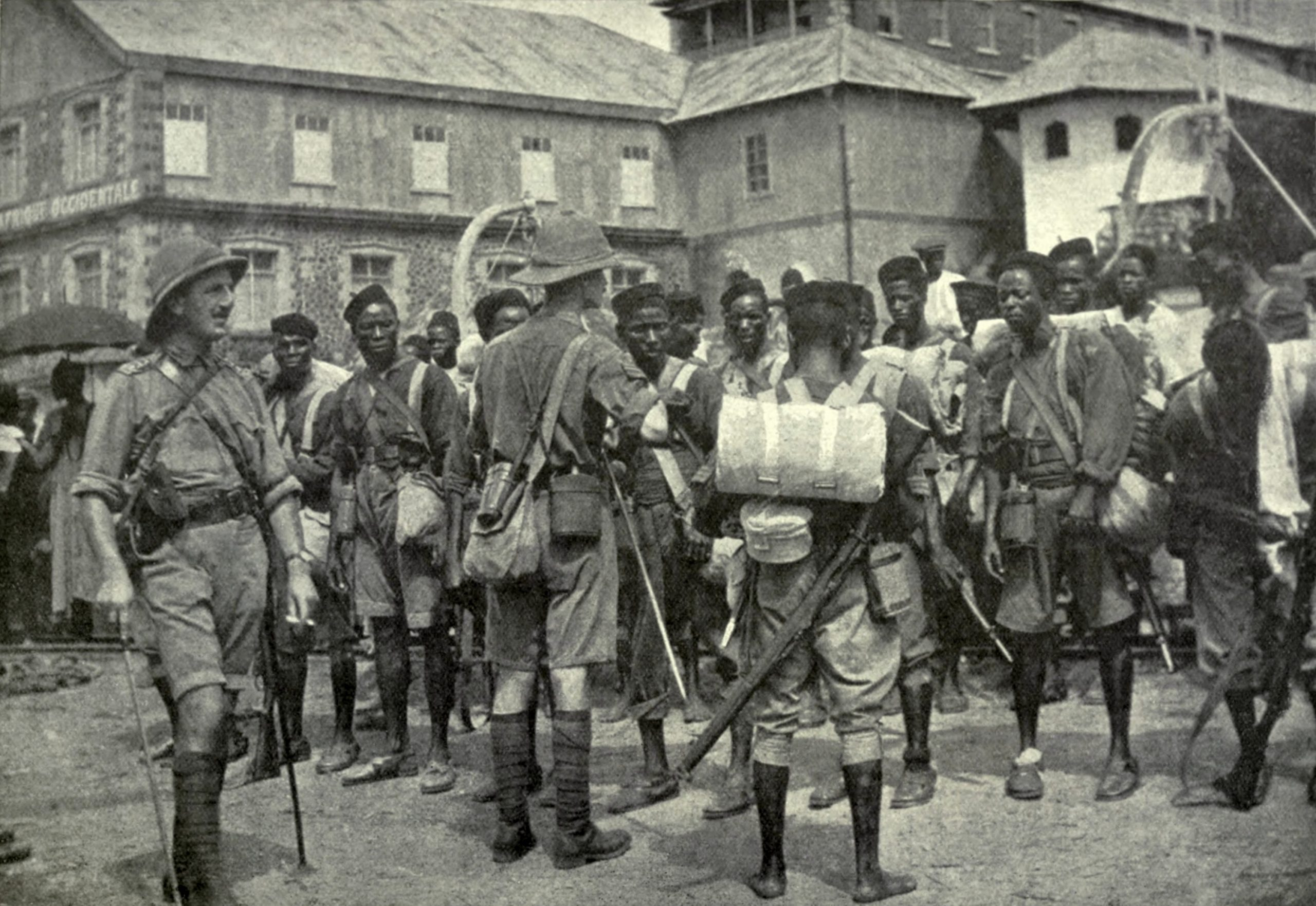 African colonial soldiers lining up in front of a white officer.