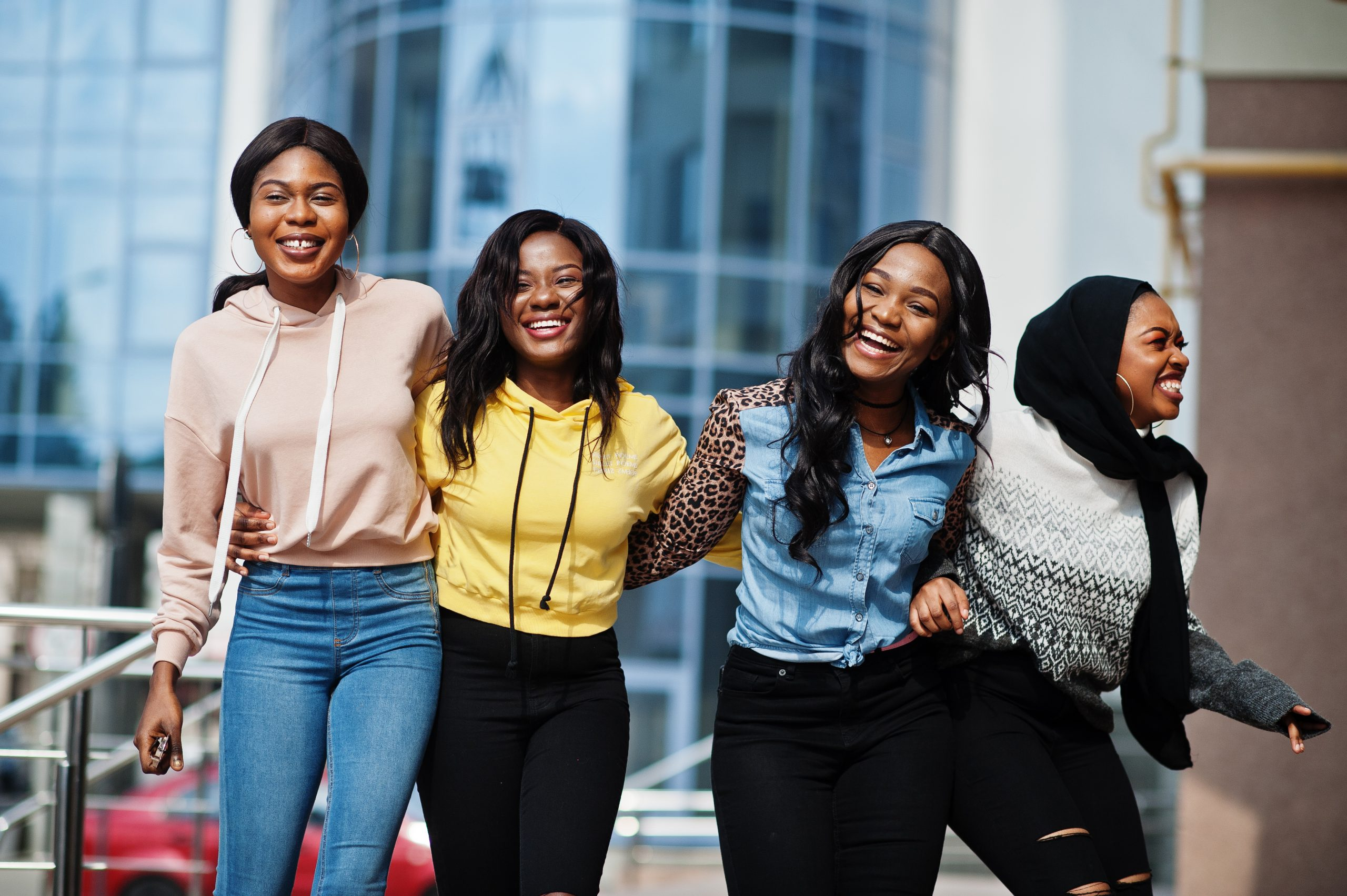 Four young female African students linking arms and laughing.